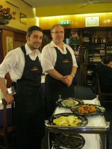 Andrea assists Ettore in serving culinary wonders