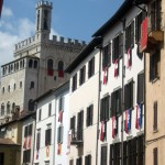 Banner-draped-homes-of-Gubbio,-backed-by-the-Palazzo-dei-Consoli