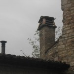 Woodstove pipes and chimneys are often in pairs on Assisi rooftops