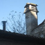 A chimney towers over a woodstove pipe