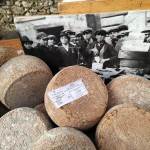 Aged_pecorino_backed_by_a_photo_of_aged_cheese_makers