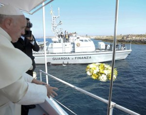 Pope Francis throws flowers on the sea from onboard a boat at Lampedusa Island